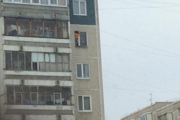 На Синих Камнях, свесив ноги из окна квартиры на восьмом этаже, сидит ребенок